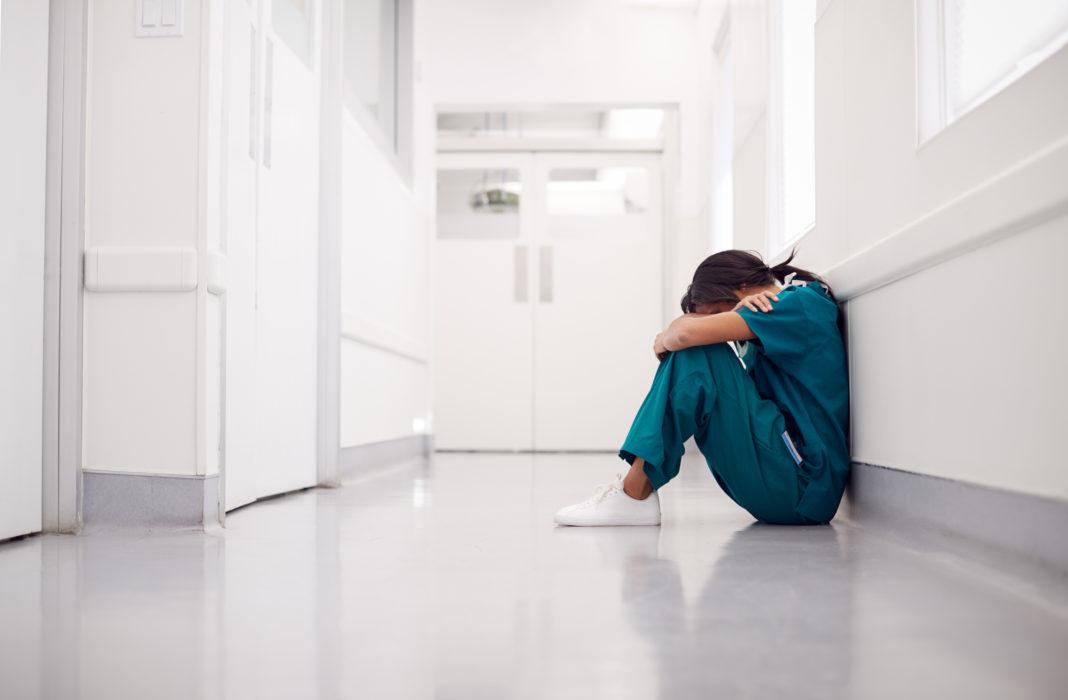Sanitaria sentada en un pasillo del hospital
